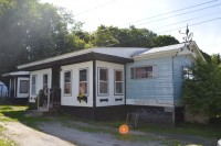 A photo of the front of a brown and blue single-wide manufactured home in Waterbury Vermont.